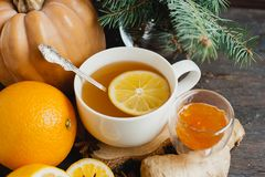 Cup of hot lemon tea with orange pumpkin and ginger jam on a wooden background. Healthy drink cold. Winter drink stock photo
