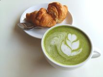 A cup of hot matcha latte so delicious with croissant. Cup of hot matcha latte so delicious with croissant Stock Image