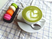 A cup of hot matcha latte so delicious with macaroon. Cup of hot matcha latte so delicious with macaroon Royalty Free Stock Photos