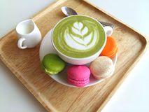 A cup of hot matcha latte so delicious with macaroon on wood. Cup of hot matcha latte so delicious with macaroon on wood Royalty Free Stock Photography
