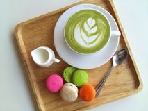 A cup of hot matcha latte so delicious with macaroon on wood. Cup of hot matcha latte so delicious with macaroon on wood Stock Photo