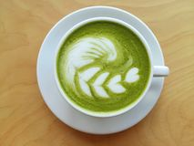A cup of hot matcha latte so delicious on wood. Cup of hot matcha latte so delicious on wood Stock Photos