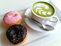 A cup of hot matcha latte and donut so delicious on white. Cup of hot matcha latte so delicious on white Royalty Free Stock Photo