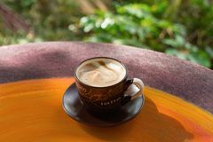 Cup with hot milk coffee on a colorful wooden table in a cafe. Dalat, Vietnam Royalty Free Stock Photo
