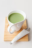 Cup of hot milk green tea on white table Stock Images