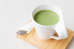 Cup of hot milk green tea on white table Royalty Free Stock Photos