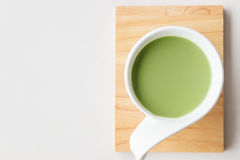 Cup of hot milk green tea on white table Stock Photography