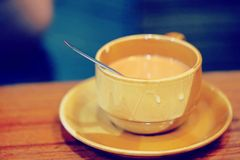A cup of hot milk tea, hot beverage in a brown cup on wooden table with blurry background. A cup of hot milk tea, hot beverage in a brown cup on wooden table Stock Photography