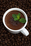 cup of hot mint chocolate on the background of coffee beans Stock Photography