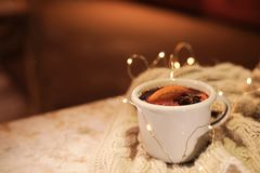 Cup of hot mulled wine and garland on table against blurred background. Space for text royalty free stock photos