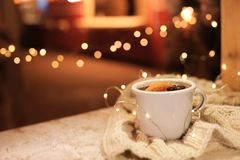 Cup of hot mulled wine and garland on table against blurred background. Space for text stock photos