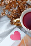 Cup of hot pink herbal tea on a windowsill. Coziness and comfort concept royalty free stock photo