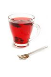 Cup with hot red carcade floral tea and teaspoon Stock Photo
