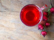 Cup of hot  roselle tea  drink on wooden table. Cup of hot  roselle tea with fresh roselle fruit in top view on wooden table with copy space for healthy herbal Stock Photo