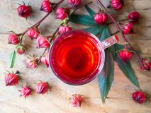 Cup of hot  roselle tea  drink on wooden table. Cup of hot  roselle tea with fresh roselle fruit in top view on wooden table  for healthy herbal drink concept Stock Photos