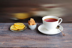 Cup of hot steaming black tea on wooden table with brown sugar and lemon. Stock Photography