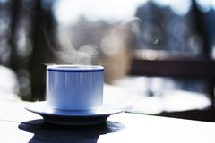 Cup of hot steaming coffee outdoors Royalty Free Stock Photo