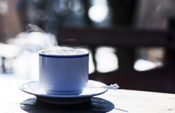 Cup of hot steaming coffee outdoors Royalty Free Stock Photography