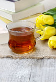 Cup of hot steaming tea on wooden table. Pile of books and bouquet of yellow tulips in the background Royalty Free Stock Photo
