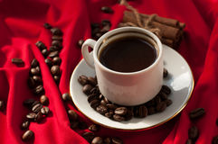 A cup of hot strong coffee, cinnamon sticks and coffee beans on a red draped fabric Royalty Free Stock Images