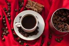 A cup of hot strong coffee, cinnamon sticks and coffee beans on a red draped fabric Stock Image