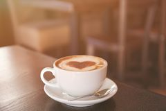 Cup with hot tasty coffee on wooden table in cafe. Close up view Stock Photo