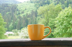Cup with hot tea. A beautiful cup with hot tea stands in front of a beautiful scenery stock photos