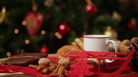 Cup of hot tea on with behind christmas tree. stock video footage