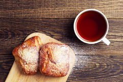 Cup of hot tea and buns Royalty Free Stock Image
