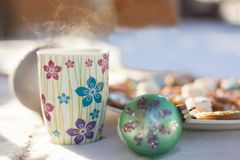 Cup of hot tea or coffe, green christmas glass ball plate. With colorful ginger cookies on snow stock images