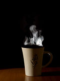 A cup of hot tea of coffee. Over black background Royalty Free Stock Photos