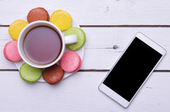 A cup of hot tea, colorful almond cookies and a smartphone on a Royalty Free Stock Images