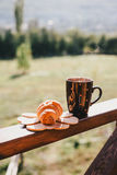 Cup of hot tea and croissant on balcony with mountains behind Stock Photography