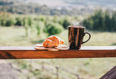 Cup of hot tea and croissant on balcony with mountains behind Royalty Free Stock Images