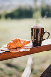 Cup of hot tea and croissant on balcony with mountains behind Stock Photos