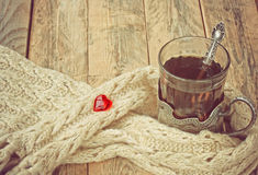 Cup of hot tea in cup holder, scarf, red heart Stock Photos