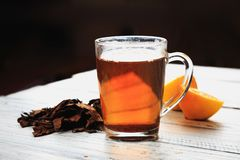 Cup of hot tea, dried tea leaves and lemon wedges stock photo