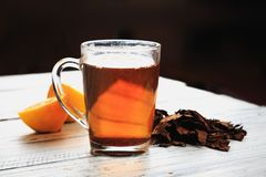 Cup of hot tea, dried tea leaves and lemon wedges royalty free stock photos