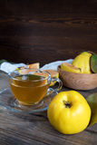 Cup of hot  tea and fresh quince fruit on table. The cup of hot  tea and fresh quince fruit on dark wooden table. An autumn still life.The cup of hot  tea and Stock Photo