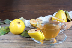 Cup of hot  tea and fresh quince fruit on table. The cup of hot  tea and fresh quince fruit on dark wooden table. An autumn still life Stock Photo