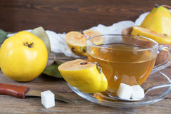 Cup of hot  tea and fresh quince fruit on table. The cup of hot  tea and fresh quince fruit on dark wooden table. An autumn still life Royalty Free Stock Image