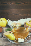 Cup of hot  tea and fresh quince fruit on table. The cup of hot  tea and fresh quince fruit on dark wooden table. An autumn still life. Coloring and processing Stock Photos