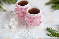 Cup of hot tea in knitted cup holder  with sweets and christmas decorations. Two cups of hot tea in knitted cup holder  with sweets and Christmas decorations Royalty Free Stock Image