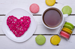 A cup of hot tea and krasochnochnoe macaroons on a wooden table. Stock Photo