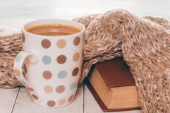 Cup of hot tea with lemon dressed in knitted warm winter scarf on brown wooden tabletop, soft focus, retro filter Royalty Free Stock Photography