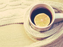 Cup of hot tea with lemon dressed in warm winter scarf on wooden background Royalty Free Stock Images