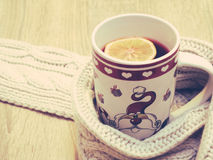 Cup of hot tea with lemon dressed in warm winter scarf on wooden background Stock Images