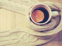 Cup of hot tea with lemon dressed in warm winter scarf on wooden background Royalty Free Stock Image