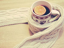 Cup of hot tea with lemon dressed in warm winter scarf on wooden background Royalty Free Stock Photos