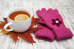 Cup of hot tea with lemon and gloves Royalty Free Stock Images